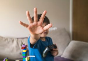 Kid showing stop gestures with his hand while holding video game console