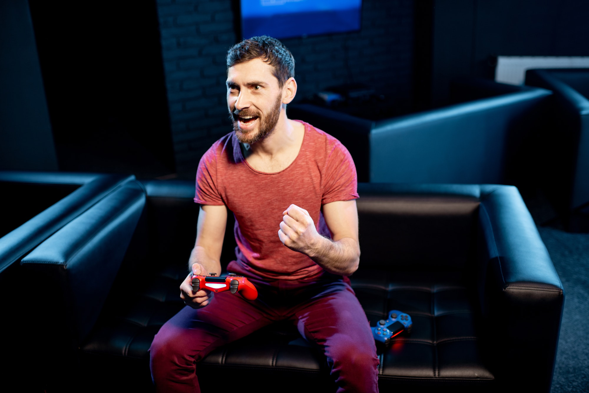 Happy man playing video games with gaming console in the club